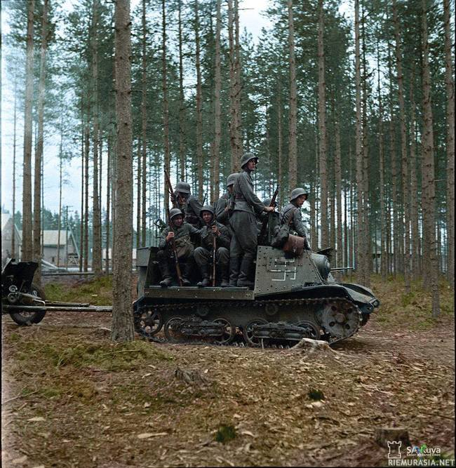 Suomalaisia joukkoja siirtymässä Venäläisellä T-20  tykistötraktorilla - Finnish troops riding on a captured Soviet T-20 Komsomolets artillery tractor.  The T-20 Komsomolets armored tractors were designed in 1936 at the Factory No. 37 in Moscow, Russia. They were powered by a GAZ-M 50hp engine and armed with one 7.62mm machine gun. During WW2, they were used to tow 45-millimeter anti-tank guns and 120-millimeter heavy mortars. They remained in production until 1941.  (Photo source - SA Kuva Finland)  (Colorized by Jared Enos from the USA)